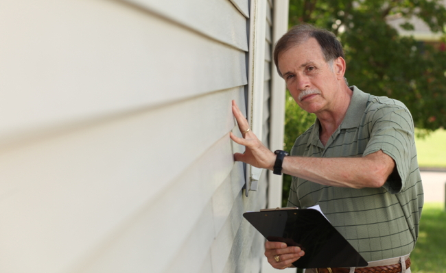 Adult male inspects siding